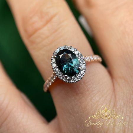 Teal-green-australian-sapphire-halo-ring-bentley-de-lisle-hand