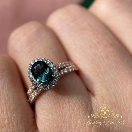 Teal-green-australian-sapphire-halo-ring-bentley-de-lisle-hand-wedding-band