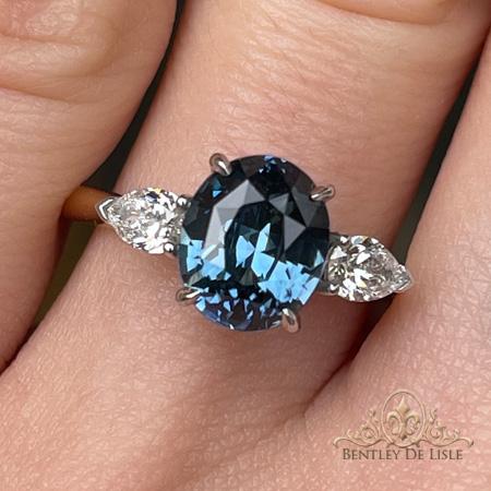 Oval-blue-sapphire-pear-diamond-ring-hand-bentley-de-lisle